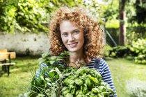 Porträt einer jungen rothaarigen Frau mit frischen Kräutern im Garten — Stockfoto