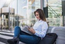 Ritratto di giovane imprenditrice seduta sulla panchina a leggere il giornale — Foto stock