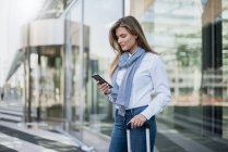 Young businesswoman with suitcase looking at smartphone — Stock Photo
