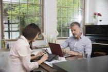 Coppia matura che lavora dal proprio ufficio, utilizzando laptop e tablet digitale — Foto stock