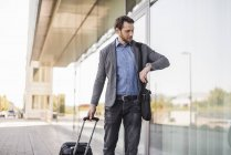 Businessman with rolling suitcase and laptop bag checking the time — Stock Photo