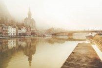 Bélgica, Dinant, paisaje urbano con el río Mosa al amanecer - foto de stock