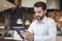 Молодой бизнесмен за планшетом в кафе — стоковое фото