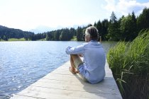 Germany, Mittenwald, mature man relaxing on jetty at lake — Stock Photo