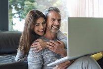 Glückliches Paar auf der heimischen Couch, das sich einen Laptop teilt — Stockfoto
