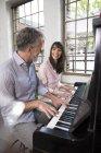 Coppia matura si diverte a casa, suona il pianoforte — Foto stock