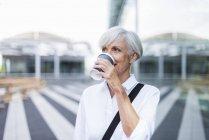 Senior businesswoman in city drinking coffee — Stock Photo