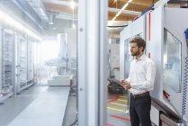Geschäftsmann mit Tablet schaut Maschine in moderner Fabrik an — Stockfoto