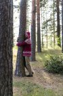 Finland, Young man hugging trees in a forest — Stock Photo