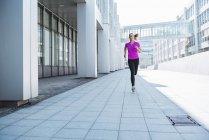Giovane donna che corre in città — Foto stock