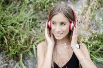Ritratto di adolescente sorridente che indossa le cuffie all'aperto — Foto stock