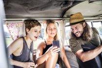 Счастливые друзья внутри фургона смотрят на смартфон — стоковое фото