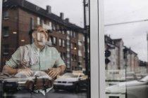 Молодой владелец бизнеса сидит в кафе и мечтает — стоковое фото