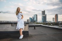 Blonde junge Frau steht auf Dachterrasse und trägt weißes Kleid — Stockfoto