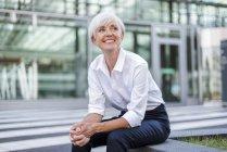 Усміхнена старша бізнесжінка сидить перед скляним фасадом і оглядаючись навколо — стокове фото