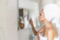 Donna avvolta in asciugamano guardando nello specchio del bagno — Foto stock