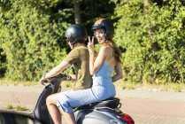 Happy couple scooter moteur d'équitation en été — Photo de stock