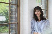 Femme debout à la fenêtre de son appartement loft, buvant du café — Photo de stock
