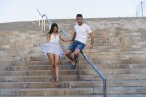 Jeune couple marchant en bas, homme glissant sur la rampe — Photo de stock