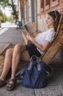 Mujer joven sentada en sillón de madera y libro de lectura en la ciudad - foto de stock