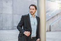 Uomo d'affari con borsa per laptop che indossa auricolari all'aperto — Foto stock