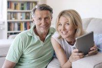 Porträt eines lächelnden reifen Paares zu Hause mit Tablet — Stockfoto