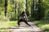 Спортсменка готовится к тренировкам на природе — стоковое фото