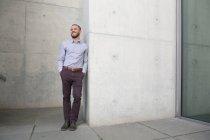Empresário confiante sorrindo encostado a uma parede — Fotografia de Stock