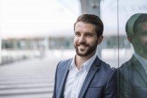Retrato de jovem empresário sorridente na fachada de vidro — Fotografia de Stock