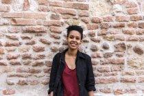 Ritratto di giovane donna sorridente davanti al muro di mattoni — Foto stock