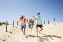Países Bajos, Zandvoort, feliz familia con hija en la playa - foto de stock