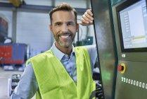 Retrato de engenheiro sorridente próximo de pé para computador na fábrica — Fotografia de Stock