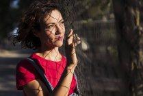 Ritratto di donna sorridente con ombra di recinzione in rete metallica sul viso guardando la distanza — Foto stock