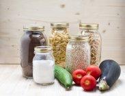 Органические овощи и макароны в стеклянных банках — стоковое фото