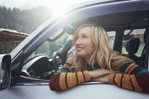 Woman sitting in car, looking at view on road trip and smiling — Stock Photo