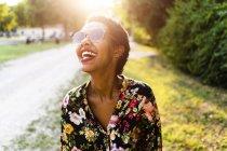 Riendo joven mujer usando gafas de sol al aire libre al atardecer - foto de stock