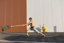 Acrobata que joga com cubeta e espanador da limpeza — Fotografia de Stock