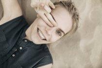 Підвищений вид, портрет молодої жінки лежачи на піску покриття очі пальцями — стокове фото