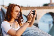 Италия, Верона, рыжая женщина, фотографирующаяся со смартфоном — стоковое фото