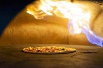 Pizza dans le four avec la flamme brûlante — Photo de stock