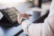 Nahaufnahme eines Geschäftsmannes mit Tablet in einem Café, der die Uhrzeit überprüft — Stockfoto