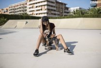 Young woman sitting on skateboard, stroking dog — Stock Photo