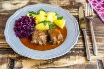 Rulade de ternera con patata y col roja en el plato - foto de stock