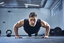Athletic man doing pushups exercise at gym — Stock Photo