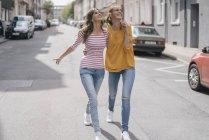 Duas amigas se divertindo na cidade, andando de braço dado — Fotografia de Stock
