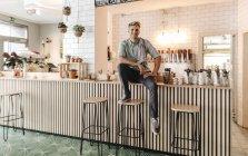 Jeune homme travaillant dans un café de démarrage et regardant la caméra — Photo de stock