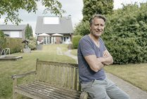 Portrait of smiling mature man leaning on bench in garden of house — Stock Photo