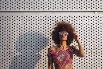 Ritratto di donna alla moda che indossa occhiali da sole specchiati contro la parete di costruzione — Foto stock