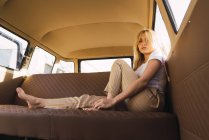Portrait of young woman sitting in a van — Stock Photo