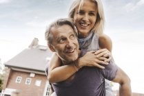 Happy mature couple having fun in front of house — Stock Photo